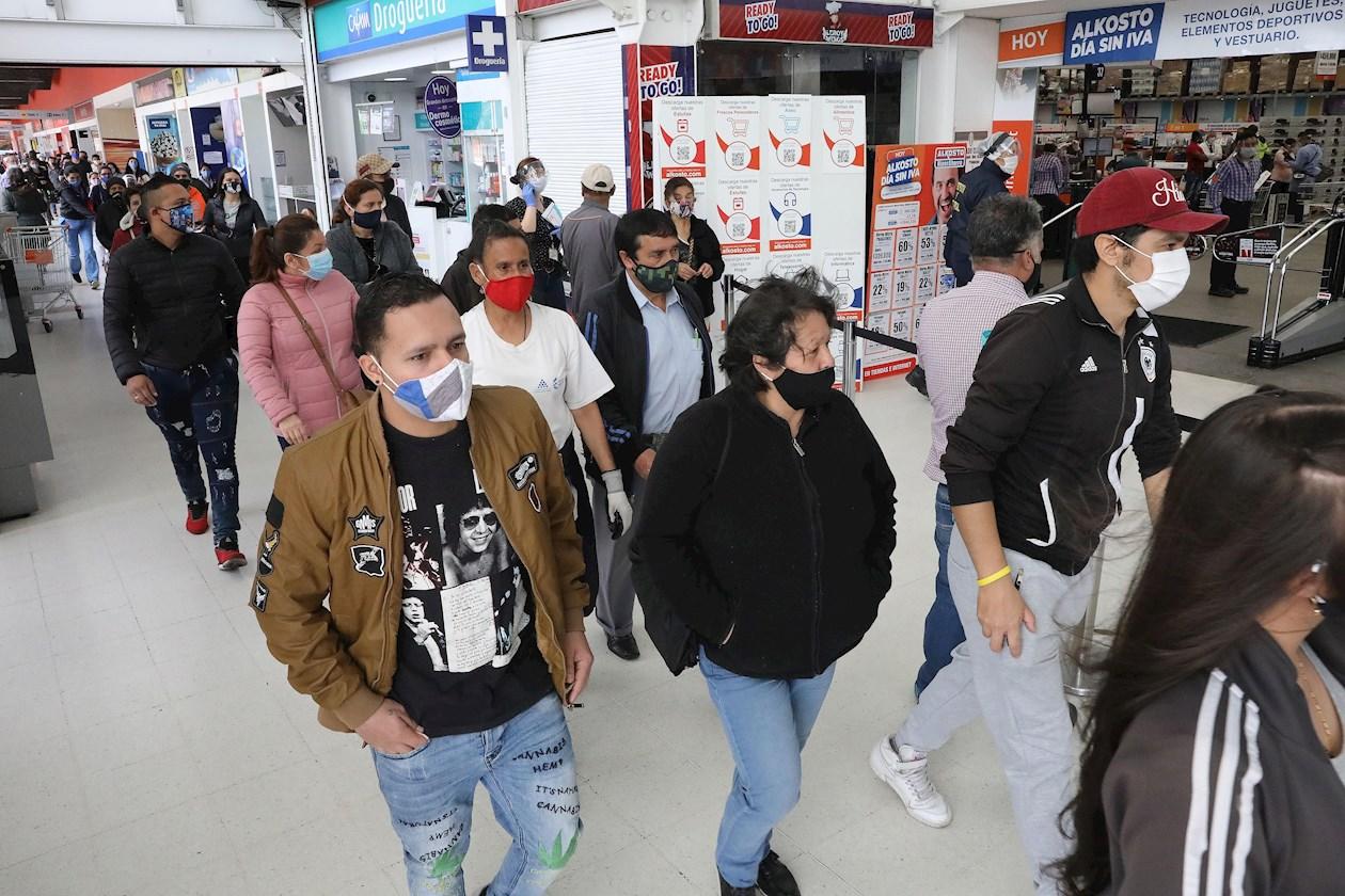 Decenas de compradores fueron registrados este viernes al hacer fila para ingresar a un almacén en Bogotá (Colombia).