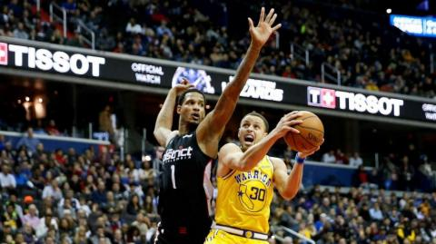 revor Ariza de los Washington Wizards (izq) defiende ante Stephen Curry.