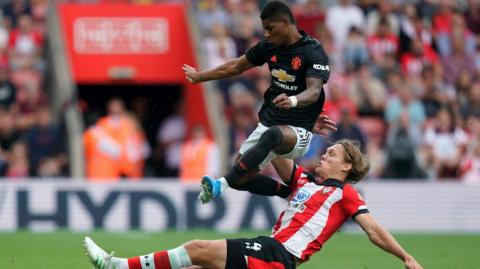 Marcus Rashford es barrido por un defensor.